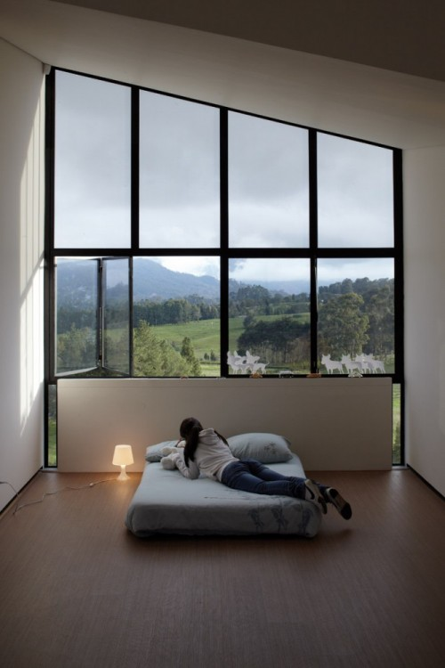 photograph of a woman on a bed before a large window looking onto a mountain vista