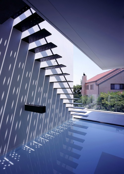 photograph of a minimalist staircase over a pool of water