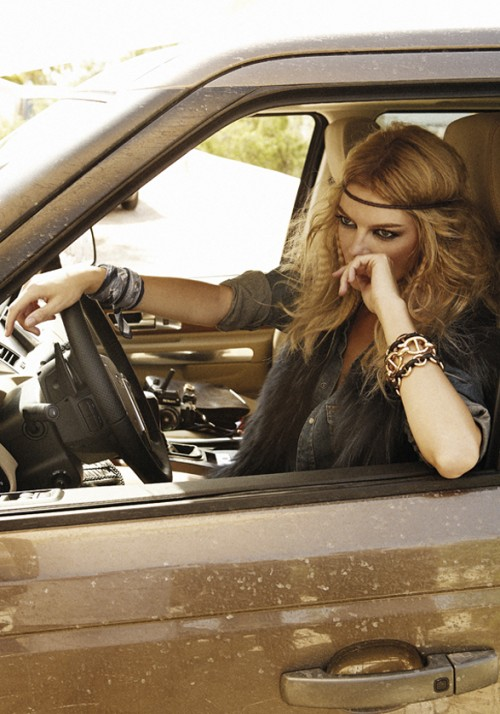 fashion shoot photo of a blonde woman dressed as a hippie at the wheel of a brown car