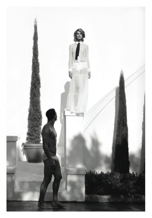 black & white picture of a woman standing on a pedestal while a man in underwear looks on from below