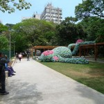 art installation in a public park of a giant sleeping monkey made out of flip-flop slippers
