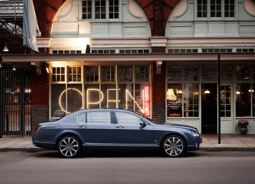 Blue Bentley Continental Flying Spur in front of a shop with a large OPEN sign