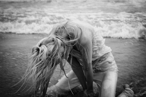 Black & white photo of a blonde woman by the beach with waves