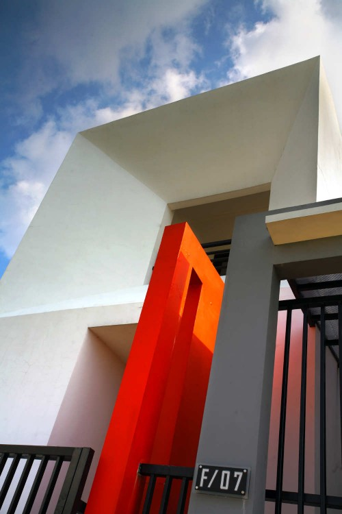 side of a white and grey building with a bright orange architectural feature