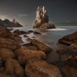 night photograph of a rocky outcrop on a coastline