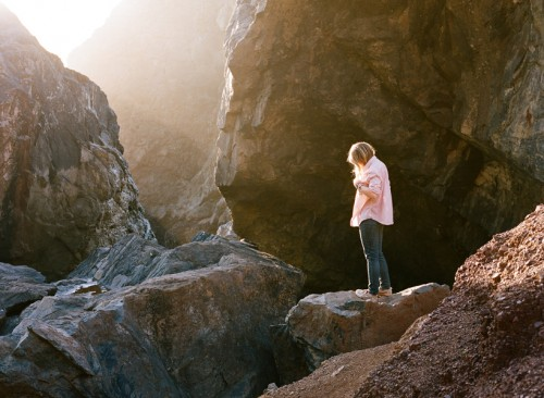 photograph of a woman standing on a rocky outcrop at sunset