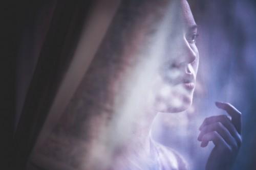 portrait photograph of a woman seen through translucent drapes