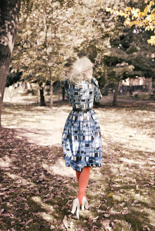 photo of a woman in a blue dress with red stockings walking amongst trees