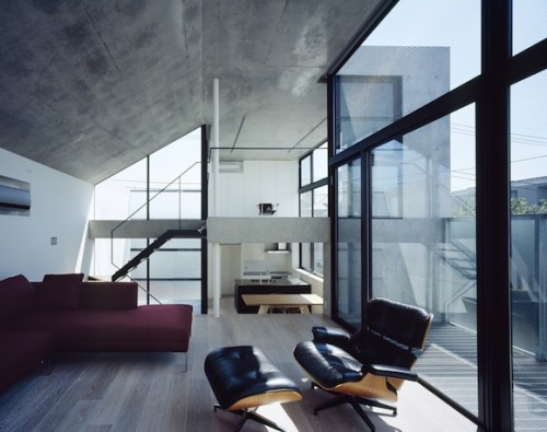 interior of house with bare concrete walls and eames chair