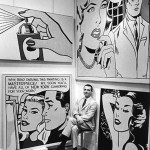 black & white photograph of Roy Lichtenstein seated before some of his works