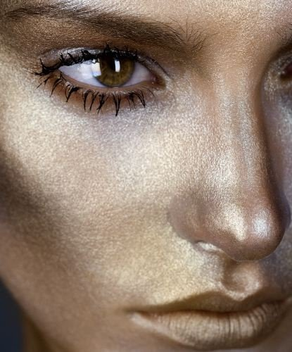 close up portrait of a woman with golden makeup