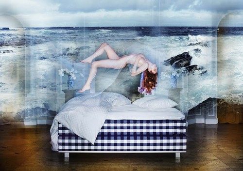 photograph of a nude woman floating over a bed