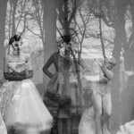 black and white photo of two models in a window with sculptures and trees reflected in the glass