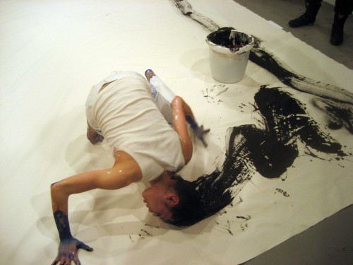 photograph of performance art of a woman painting with her hair