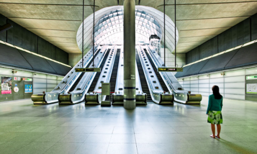 picture of a woman in a subway station near bank of escalators