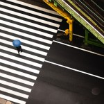 aerial photo of a man with a blue umbrella crossing zebra lines