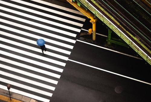 aerial photo of a man with a blue umbrella crossing zebra lines