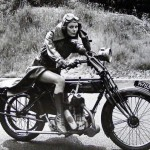 photograph of a woman in a trenchcoat and googles on a vintage bike