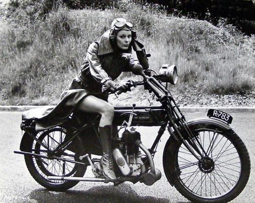 photograph of a woman in a trenchcoat and goggles on a vintage bike