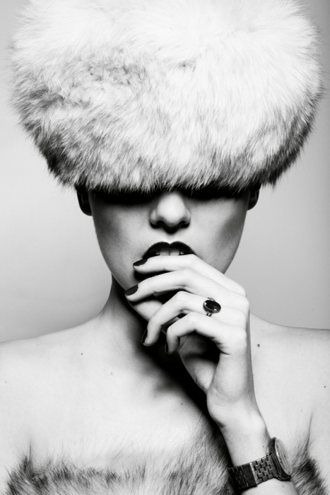 black & white picture of a woman in a fur hat biting her lip