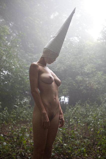 Nude girl standing with head bowed in the forest light wearing a linen-wrap mask and dunce-cap.