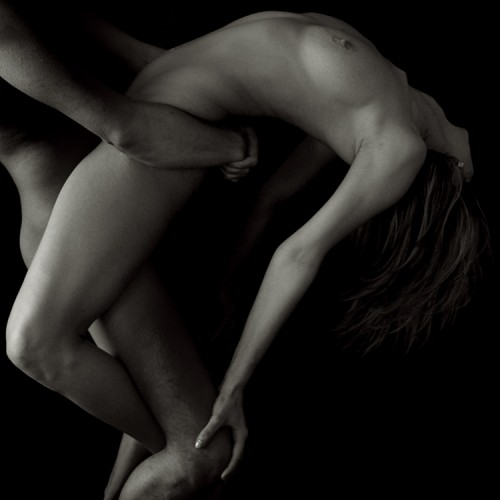 black & white photo of nude male carrying a nude female with back arched
