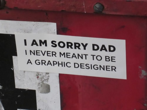 humorous sign about designers on the back of a vehicle