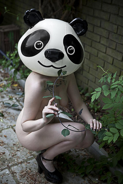 Nude girl in a blow-up panda mask crowching near a plant pretending to eat the shoots.