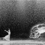 black & white photo of a ballet dancer on a stage filled with water, rain and rocks
