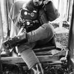 Stanley Kubrick looking bored holding a film camera