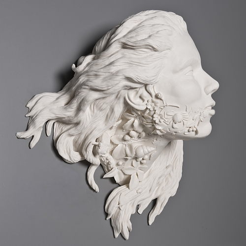 White porcelain bust of a woman's face with flowing hair, flora growing out of her neck.