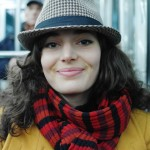 photo of a woman on paris metro wearing hat, scarf and coat