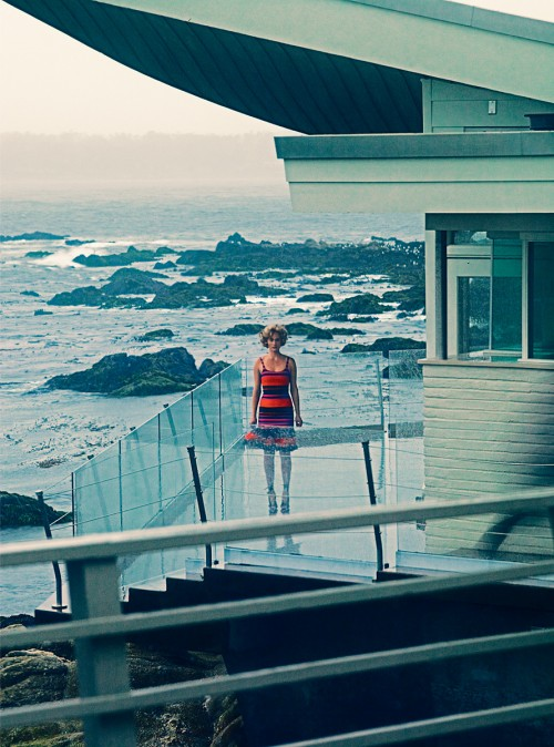 woman standing in balcony of beachside house