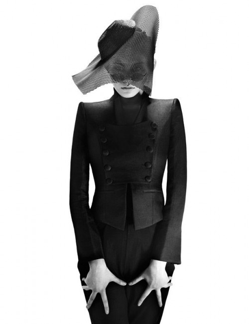 woman in black outfit with futuristic hat with incorporated veil