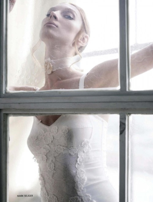 woman in white dress and veil with face against window