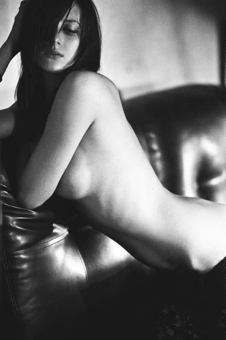 woman leaning against leather couch