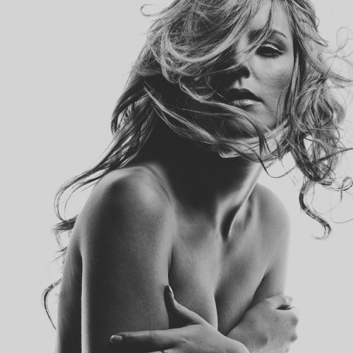 Black and white photo of topless woman with tousled blonde hair covering her breasts with her hands.