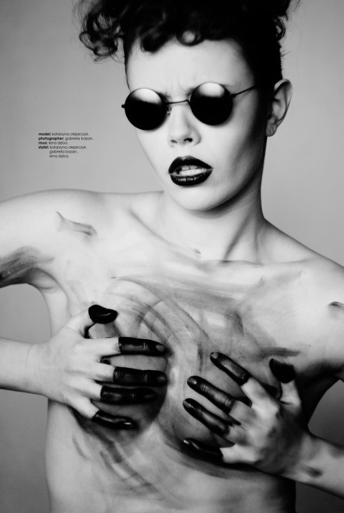 Topless model wearing dark shades and rubbing her paint-dipped fingers on her chest.
