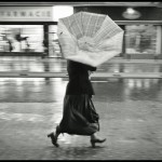 woman walking in street with upturned umbrella
