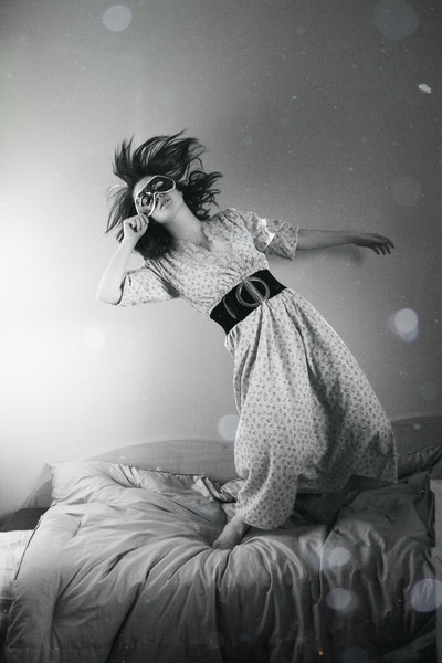 Masked woman falling on bed