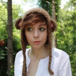 Girl wearing a monkey hat in a forest