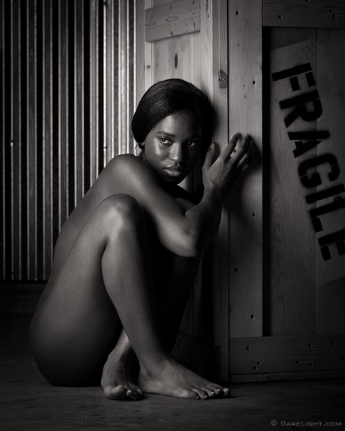 Dark-skinned nude model seated next to a crate marked Fragile