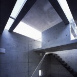 interior of raw concrete house with shafts of light