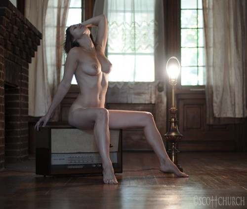 Nude model posing on a vintage radio near a naked table lamp