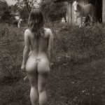 Nude model in a field near a horse stable