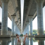 Pair of nude models under a bridge