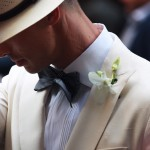man in linen suit adjusting hat