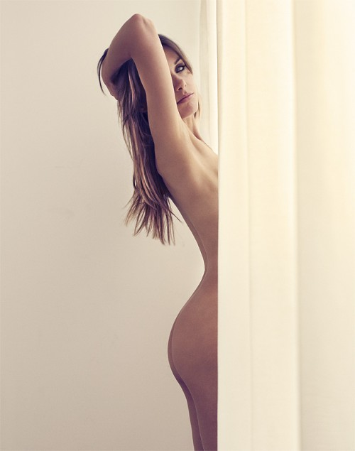 Nude model behind curtains