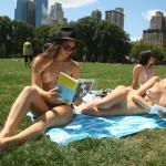topless women in hats reading books in central park