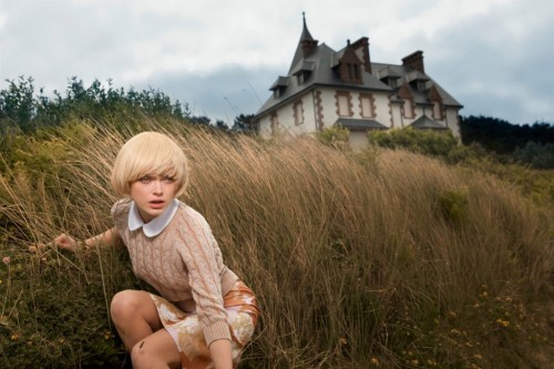 sophie vlaming crouched in grass near house, wide shot